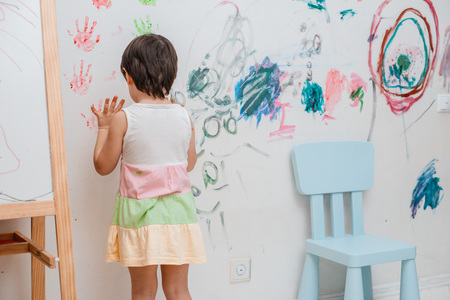 A little girl, 3 years old, painted an arched look with paint and a brush on the wall of her room. Naughty child, messing around indulge in hooligans. Childhood free space