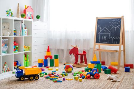 Sala de juegos para niños con juguetes de bloques educativos de plástico de colores. Piso de juegos para jardín de infancia de preescolares. habitación infantil interior. Espacio libre. maqueta de fondo pizarra Foto de archivo