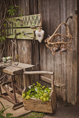 design of the photo zone in a rustic style, old wooden doors and boards with tools and spring flowers. Art space in the garden. the gardeners workshop