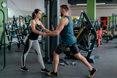 Fitness girl lifting dumbbell in morning with assistance of her personal trainer at public gym. concept of a healthy lifestyle. Sports physical development. maintaining the physical strength of youth