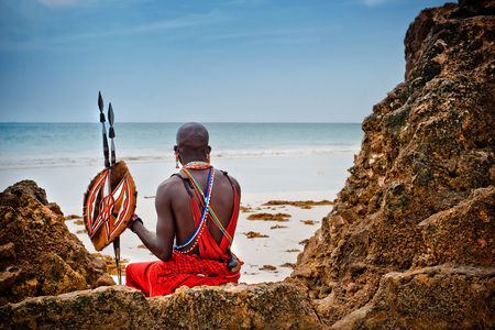 African man of the Maasai tribe in Kenya sits on the ocean and looks into the distance. The flavor of the journey. Travel Culture Foto de archivo