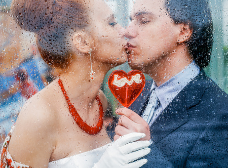 Loving couple kissing on the lips view through the wet glass in the drops after the rain. Wedding staged photography. the bride and groom kiss and hold a heart caramel. Romantic date.