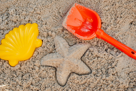 Children toys for build the sandcastle, Shovel, Molds laying on the sand at the seashore, Creative summer activity on vacation Banco de Imagens