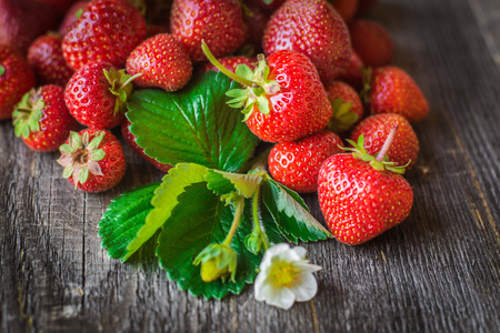 strawberry is scattered from a basket on wooden background Banco de Imagens