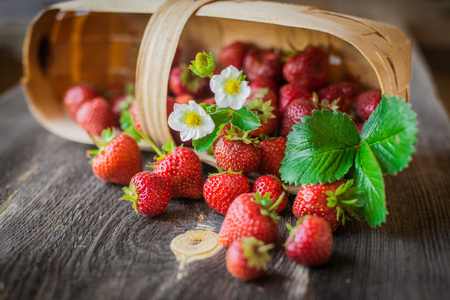 Strawberries lie in a basket on a wooden background. Useful fresh berry from the garden.
