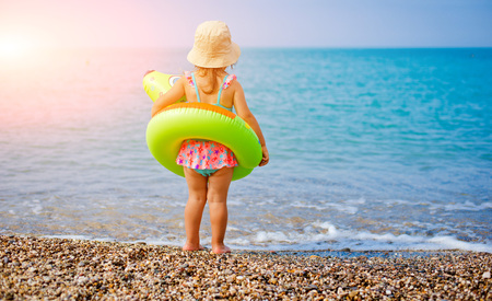 Happy little girl child bathing with inflatable circle and having fun in the sea