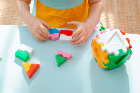 close-up of the childs hands collect puzzle sorter. Cube with inserted geometric shapes and colored plastic blocks. Educational childrens game toy Banco de Imagens