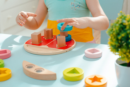 little girl collects wooden multi-colored sorter Safe natural wooden kids toys Educational game