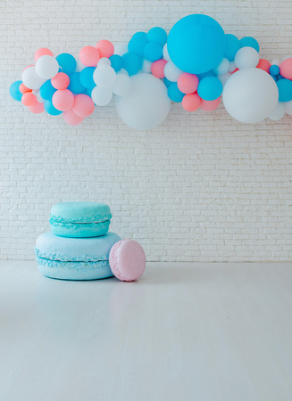 balloons ice cream cart on festive white brick background with Bright blue pink background with free space giant macaroons Event childrens party space text sweets, holiday treats