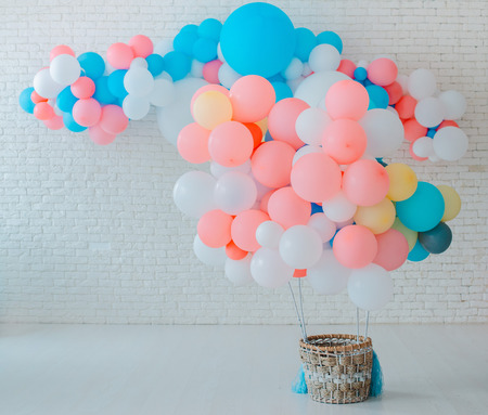 balloons basket for air flight on white brick background with bright blue pink background with free space, event childrens party space text sweets, holiday decorations blue pink Banco de Imagens