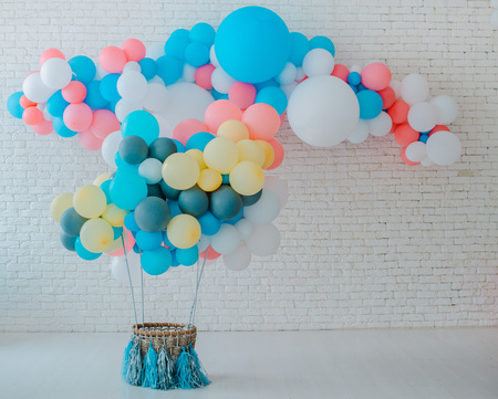 balloons basket for air flight on white brick background with bright blue pink background with free space, event children's party space text sweets, holiday decorations blue pink