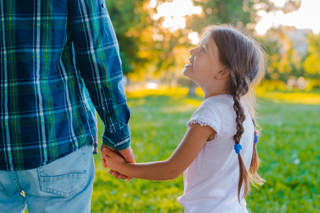 little girl kid daughter holding her fathers hand background nature sunset. The concept of parental care and happy carefree childhood. Children under the protection of an adult. fathers day