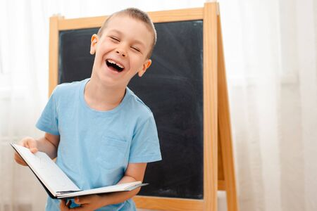 schoolchild stands and laughs at the blackboard with an open notebook. Preparation for school. A boy on a black and white background with an open book smiles. Chalk Board