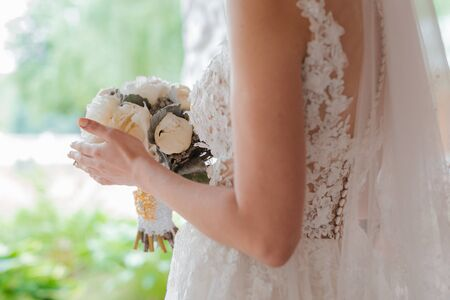 Newly married couple. Wedding day. Bouquet of the bride in the hands, the groom's embrace. Free space.