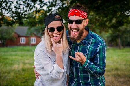 Funny man, woman with protruding tongues in rocker style scream. Family of fun hipsters fooling around outdoors in nature. love, married couple