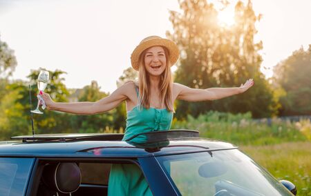 Cheerful girl woman rejoices with a glass of wine leaning out of the hatch of the car at a party in the summer in nature. The concept of leisure, travel, holiday, alcohol.