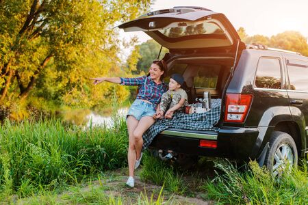 mother woman and child son comfortably relax in nature by the river sitting on the trunk of a jeep. Family travel and tourism by car. Concept of freedom, vacation, summer, lifestyle, sunset