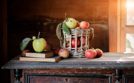 Fresh harvest of ripe and healthy farm apples in a glass jar, in a basket. Still life autumn rustic by the window and an old chest of drawers on a dark background. Standard-Bild - 129167087