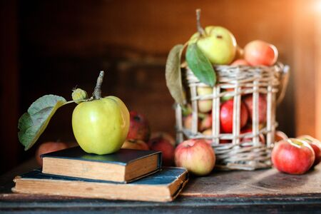 Fresh harvest of ripe and healthy farm apples in a glass jar, in a basket. Still life autumn rustic by the window and an old chest of drawers on a dark background. Standard-Bild - 129167260
