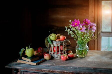 Fresh harvest of ripe and healthy farm apples in a glass jar, in a basket. Still life autumn rustic by the window and an old chest of drawers on a dark background. Standard-Bild - 129167262