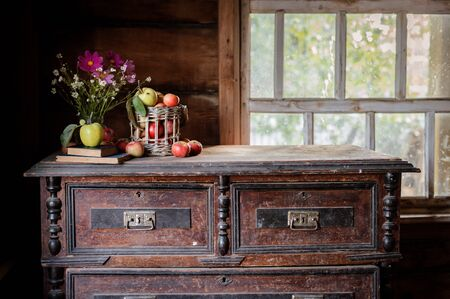 Fresh harvest of ripe and healthy farm apples in a glass jar, in a basket. Still life autumn rustic by the window and an old chest of drawers on a dark background. Standard-Bild - 129167259