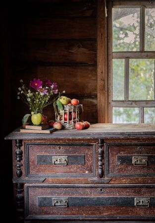 Fresh harvest of ripe and healthy farm apples in a glass jar, in a basket. Still life autumn rustic by the window and an old chest of drawers on a dark background. Standard-Bild - 129167265