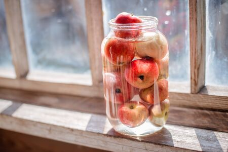 Fresh harvest of ripe and healthy farm apples in a glass jar, in a basket. Still life autumn rustic by the window and an old chest of drawers on a dark background. Standard-Bild - 129167281