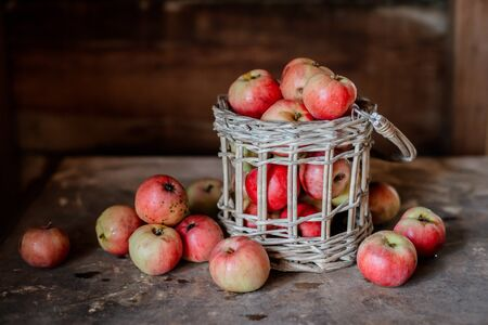 Fresh harvest of ripe and healthy farm apples in a glass jar, in a basket. Still life autumn rustic by the window and an old chest of drawers on a dark background. Standard-Bild - 129167269