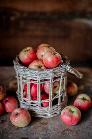 Fresh harvest of ripe and healthy farm apples in a glass jar, in a basket. Still life autumn rustic by the window and an old chest of drawers on a dark background. Standard-Bild - 129167276