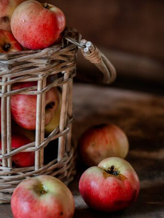 Fresh harvest of ripe and healthy farm apples in a glass jar, in a basket. Still life autumn rustic by the window and an old chest of drawers on a dark background. Standard-Bild - 129167273