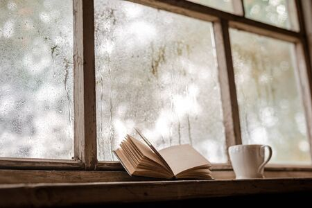A white Cup and old books on the background of a rustic wooden wet window, copy space. Hot drink for autumn cold rainy days. The concept of Hygge, autumn mood. selective focus Stockfoto