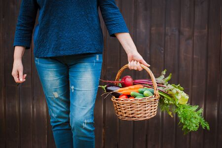 Basket of vegetables in the hands of a farmer on a wooden. The concept of a healthy lifestyle and ecological nutrition. raw food diet Standard-Bild - 129167798