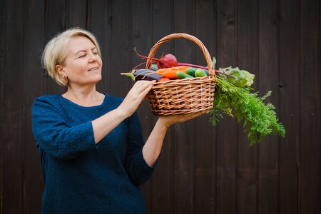 Woman 50-60 years old pensioner farmer holding a basket with organic vegetables grown in his garden. On a dark wooden background. Healthy diet. eco Standard-Bild - 129167803