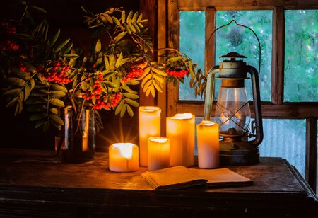 Still life with burning candles old country house near a wooden wet window in the autumn evening. The concept of mysticism, fortune telling, Halloween, magic, romance. Old kerosene lamp, book, Rowan.