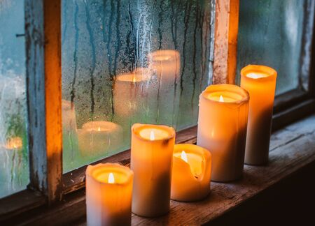 beautiful background with raindrops on the window and burning candles. twilight rainy summer or autumn evening. Old rustic wooden window and raindrops texture, wet glass