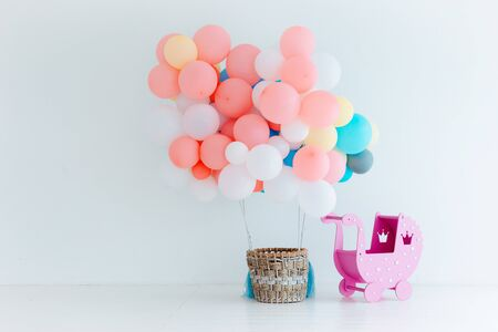 Festive pink balloons with basket on white background. Congratulations on the newborn. Childrens birthday party. Free space for text. horizontal. Baby girl . Reklamní fotografie