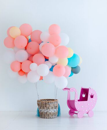 Festive pink balloons with basket on white background. Congratulations on the newborn. Children's birthday party. Free space for text. vertical Baby girl . Stock Photo