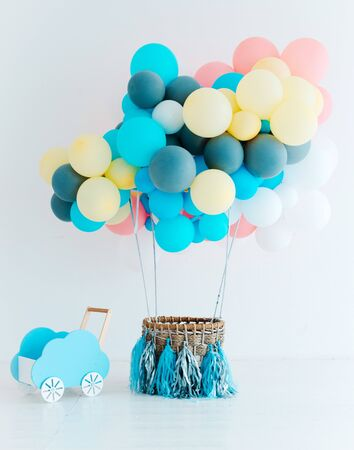 Festive blue balloons with basket on white background. Congratulations on the newborn. Children's birthday party. Free space for text. Baby boy. vertical
