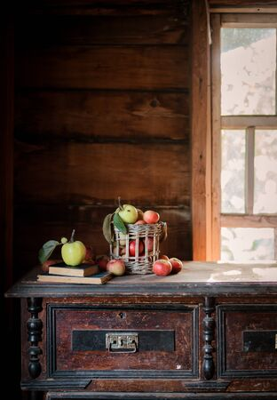 Fresh harvest of ripe and healthy farm apples in a glass jar, in a basket. Still life autumn rustic by the window and an old chest of drawers on a dark background. Standard-Bild - 129168280
