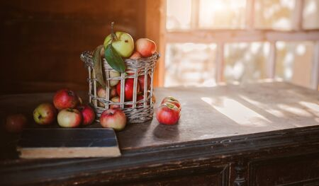 Fresh harvest of ripe and healthy farm apples in a glass jar, in a basket. Still life autumn rustic by the window and an old chest of drawers on a dark background. Standard-Bild - 129168277