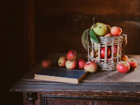 Fresh harvest of ripe and healthy farm apples in a glass jar, in a basket. Still life autumn rustic by the window and an old chest of drawers on a dark background. Standard-Bild - 129168278