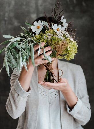 bouquet of white flowers in a glass jar in the hands of a girl florist on the background of a concrete wall. The concept of inspiration, congratulations, spring, decoration with flowers. Reklamní fotografie