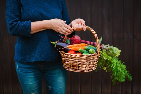 Basket of vegetables in the hands of a farmer on a wooden. The concept of a healthy lifestyle and ecological nutrition. raw food diet Standard-Bild - 129168479