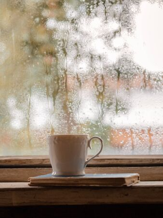 A white Cup and old books on the background of a rustic wooden wet window, copy space. Hot drink for autumn cold rainy days. The concept of Hygge, autumn mood. Stockfoto