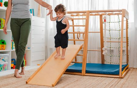 Mom supports a child aged 1.5 years engaged in a home childrens wooden sports complex with a slide. Early development of physical activity of the child.