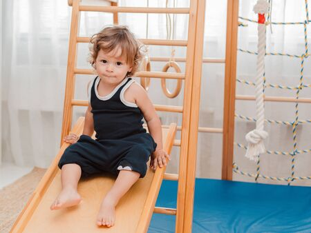 child at an early age of 1.5 years is engaged in the home childrens wooden sports complex with a slide . Early physical active development of the child.