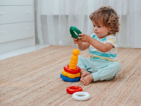 baby plays on the floor in the room in educational plastic toys. The development of children at an early age. Kindergarten, nursery. Toddler 版權商用圖片