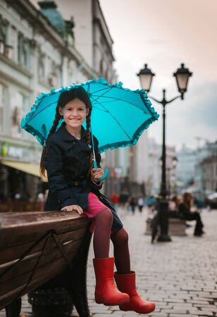 Little girl 6 years old child with an umbrella in rubber boots having fun on a bench in the center of Moscow in the fall or spring. Off-season. Autumn and spring urban fashion. Old street, paved road