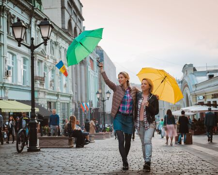 Portrait of two close friends walking together on a city street in Moscow. They both carry colorful bright umbrellas from rain and happily look around. Girlfriends, hipsters
