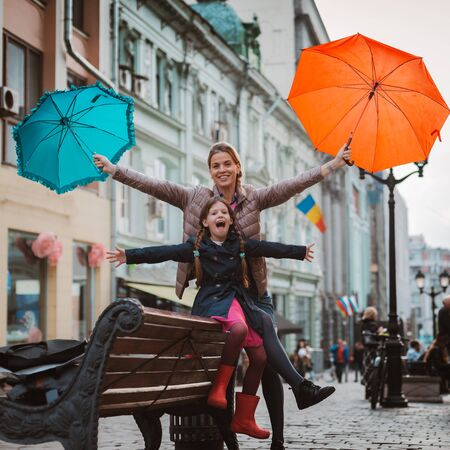 Little girl 6 years old child with an umbrella in rubber boots having fun with her mother on a bench center Moscow in the fall or spring. Autumn spring urban fashion. Family outing. Zdjęcie Seryjne